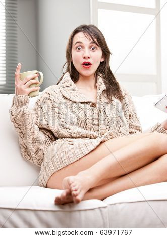 Astonished Girl With A Mug And A Tablet