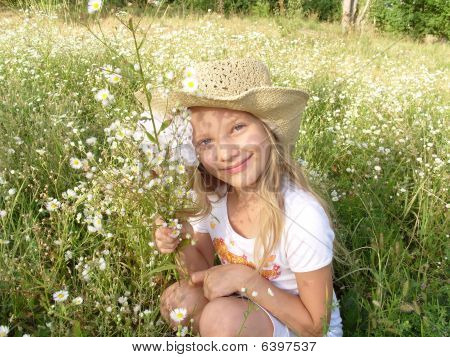 Image of Little girl sitting among wildflowers on the field