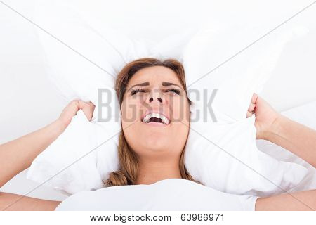 Woman In Bed Covering Ears With Pillow Because Of Noise
