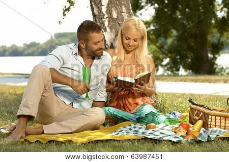 Happy casual couple reading book at picnic, outdoor. Attractive caucasian blonde woman, handsome man, basket, cloth, smiling.