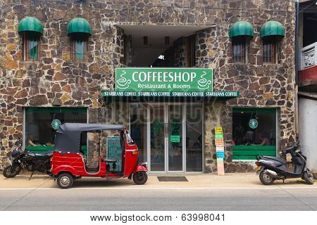 HIKKADUWA, SRI LANKA - FEBRUARY 20, 2014: Red tuk-tuk vehicle parked in front of coffee shop. In Asia, small outlets try to copy big brands, in this case like Starbucks coffee.