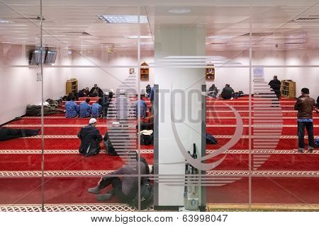 DOHA, QATAR - FEBRUARY 18, 2014: Muslim men praying in one of 13 prayer rooms at Doha International Airport, the only commercial airport in Qatar.