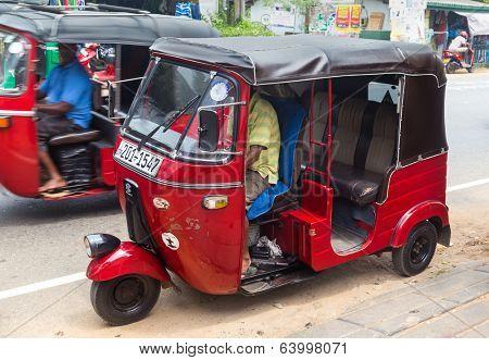HIKKADUWA, SRI LANKA - FEBRUARY 20, 2014: Two red tuk-tuk vehicles on street of Hikkaduwa. Tuk-tuks are very popular way of sightseeing the town.