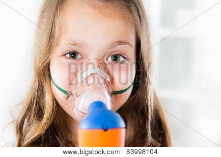 Little girl using an inhaler indoors
