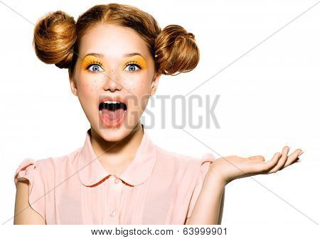 Beauty Surprised Teenager Model Girl. Beautiful Joyful teen girl with freckles, funny red hairstyle and yellow makeup. Open hand. Professional make up. Isolated on a white background
