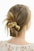 stock photo of messy  - Studio shot of young woman with casual messy chignon hairstyle - JPG
