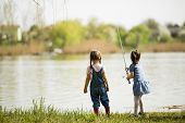 foto of fish pond  - Two little girls fishing at sunny day