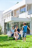 stock photo of lawn grass  - happy family in front of big modern new house outdoors - JPG