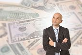stock photo of brazilian money  - Attractive Happy Young Business Man with bald head Thinking and Dreaming of Big Money over Dollar Currency Background - JPG