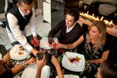 stock photo of restaurant  - Group of people at a restaurat having dinner being served by a waiter - JPG