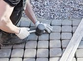 foto of banquette  - mason worker making sidewalk pavement with stone blocks - JPG