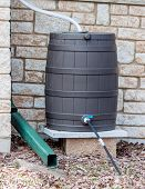image of downspouts  - A rain barrel set up to catch rain - JPG