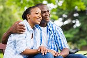 stock photo of daydreaming  - cute young african american couple daydreaming in forest - JPG