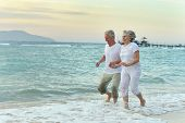 stock photo of old lady  - Nice old couple running on sea beach - JPG