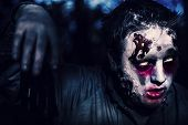 stock photo of moonlit  - Creepy night photo of a scary zombie looking gravely ill with infectious facial wounds walking through moonlit forest - JPG