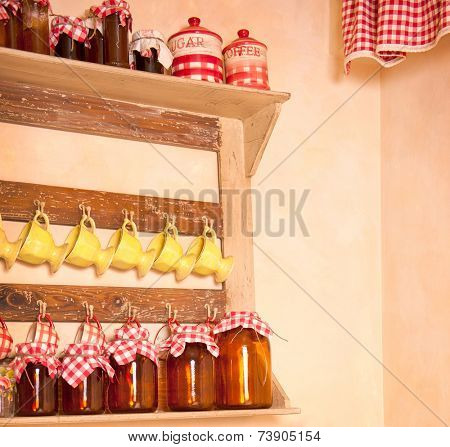 Retro style rustic cupboard with condiments, cups and cans.