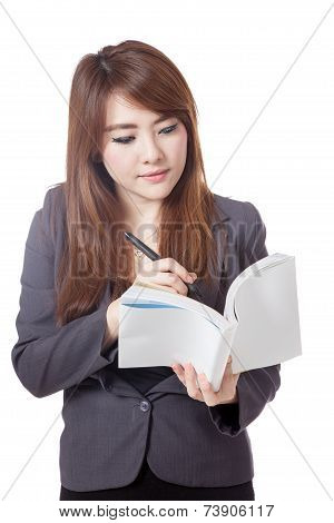 Asian Businesswoman Is  Thinking And Writing Note In A Book