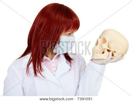Woman In Medical Uniform Looks At Human Skull