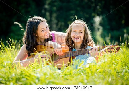 Mother teaching daughter playing guitar