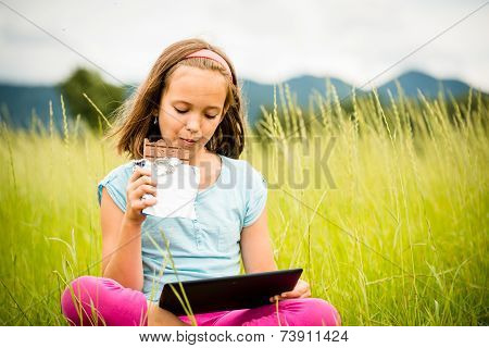 Girl enjoying chocolate and watching tablet