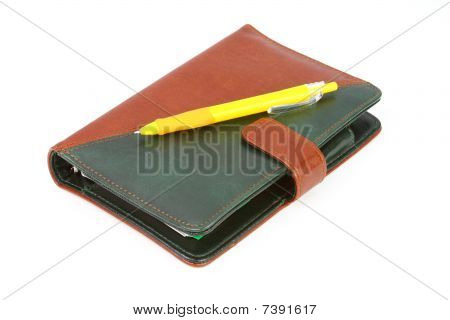 Closed Leather Office Organizer And A Yellow Pen