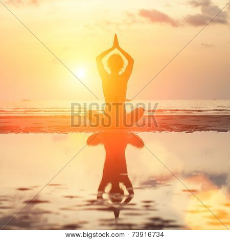 Silhouette young woman practicing yoga on the beach at surrealistic sunrise.