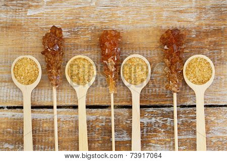 Brown sugar on wooden spoons and brown sugar sticks on wooden surface