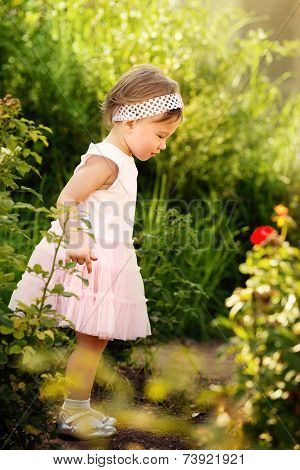 Little Girl Standing In A Garden