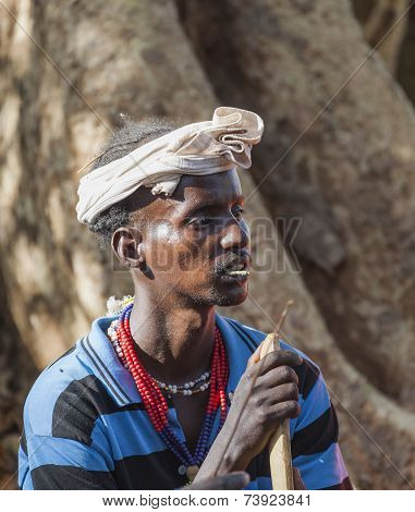 Traditionally Dressed Hamar Man With Chewing Stick In His Mouth At A Bull Jumping Ceremony.