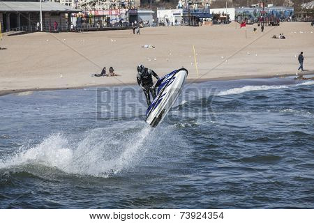 Coney Island New york  April 14:  Man on jetski jumping waves on coney Island beach April 14 2011 Coney Island beach is from West 37th St. at Sea Gate to the beginning of Manhattan Beach about 2.5mi.