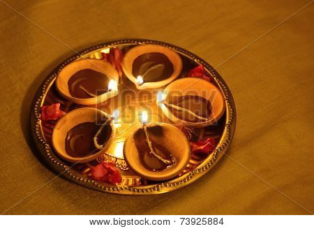 A set of earthen indian lamps in a brass plate. Festive objects.