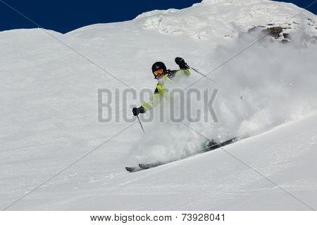 Alpine skier skiing downhill, blue sky on background