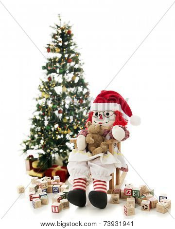 A rag doll rocking her toy bear in her Santa hat.  She's in front of a lighted Christmas tree and surrounded by scattered alphabet blocks.  On a white background.