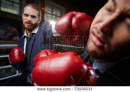 Aggressive businessman hitting his rival