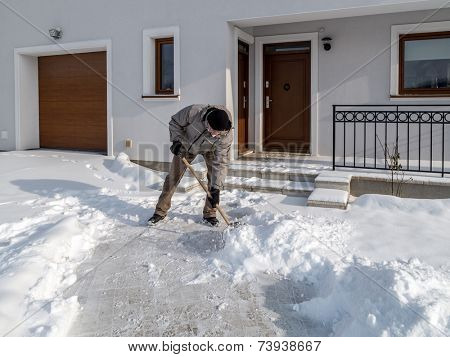 Man clearing path to his house of snow with shovel after heavy snowing