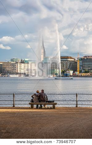 Two people look at the fountain in the center of Hamburg.