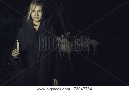 Young woman with candle in the forest