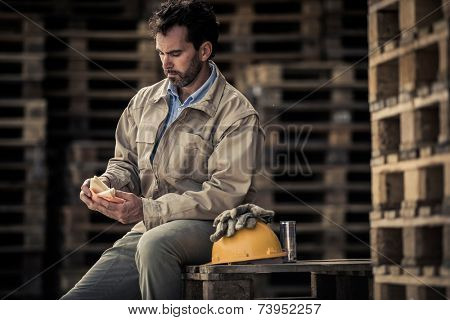Warehouse worker sitting on pallets for a lunch break