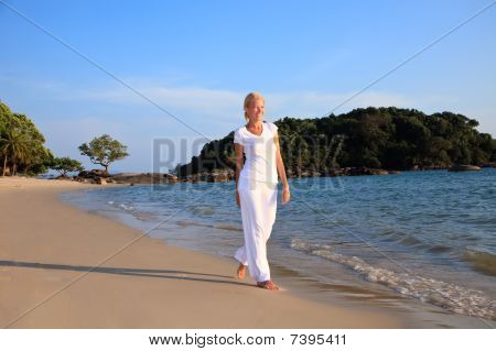 Woman Taking A Walk On The Beach