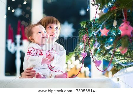 Happy Laughing Kids, A School Age Boy And His Baby Sister, Playing Together At A Beautiful Christmas