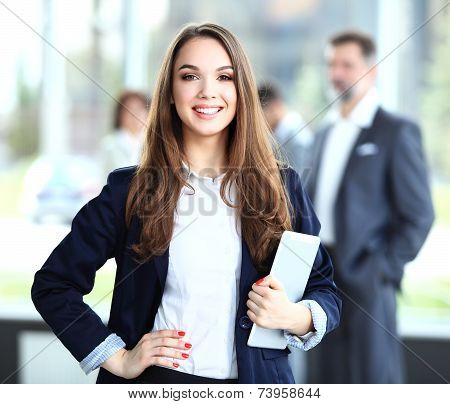 Business woman standing in foreground with a tablet