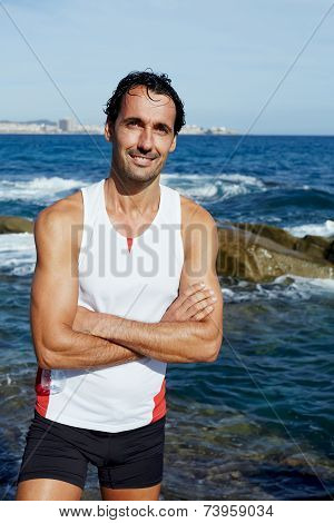 Portrait of smiling runner standing on rocks at sunny day