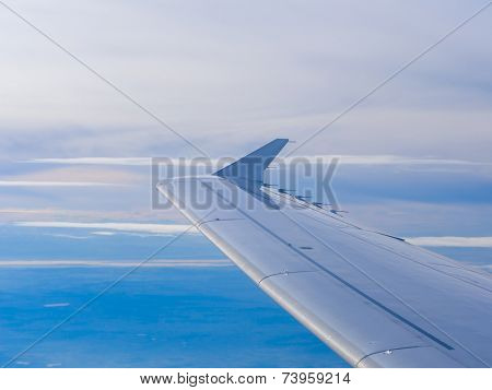 Wing of an airplane flying above the clouds. people looks at the sky from the window of the plane