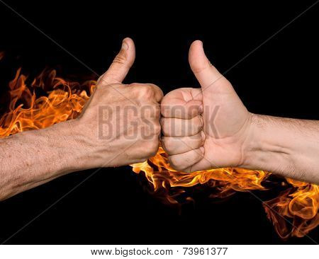 Two Men Bumping Fists With Thumbs Up Against The Fire Flames