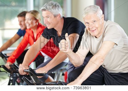 Happy senior man in gym on bike holding his thumbs up