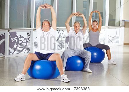 Group of senior people stretching in gym on exercise balls