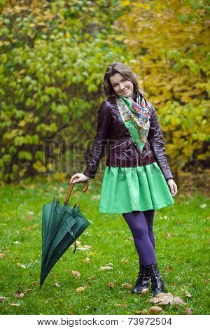 Woman with green umbrella smiling as raining, against green of autumn park