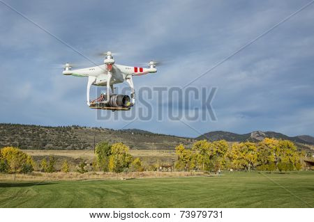 FORT COLLINS, CO, USA, October 15, 2014:  Airborne radio controlled Phantom quadcopter drone flying over park at foothills with a camera mounted on a home made platform.