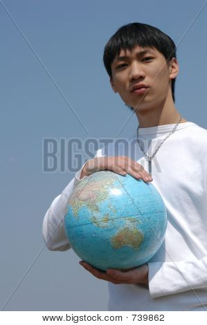 Young Asian Man With A Globe