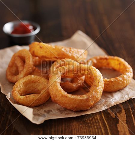 crispy onion rings with ketchup on parchment paper